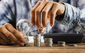lampadina e pile di monete