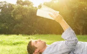 ragazzo sdraiato sull'erba che prende il sole leggendo progetto
